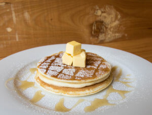 a stack of pancakes with butter and syrup from fresh pressery cafe