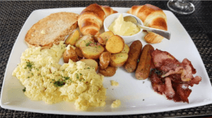 breakfast plate of eggs, potatoes, bacon and sausage